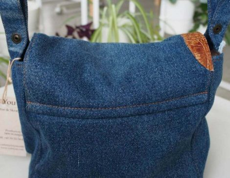 Classic blue denim cotton decorated with two pieces of brown leather imitating reptile skin.